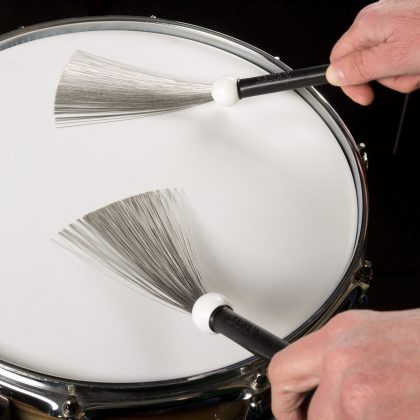 Two beat brushes played on a drum